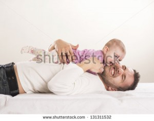 stock-photo-young-father-is-having-fun-with-his-little-baby-131311532